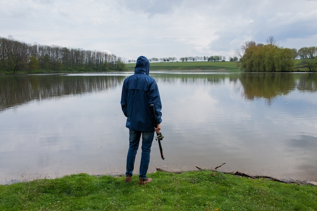 Homem jovem, com, um, cana de pesca, ficar, ligado, a, lago Foto Premium