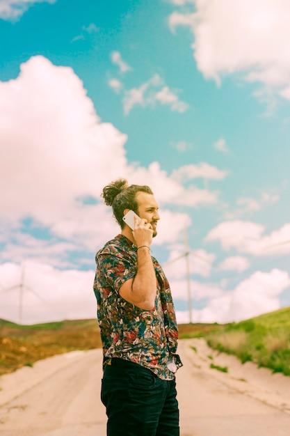 Homem jovem, comunicando-se, ligado, smartphone, ligado, natureza Foto gratuita