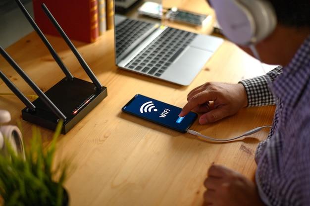 Homem jovem, conectando, roteador, wi-fi, ligado, smartphone, para, internet, e, social, mídia Foto Premium