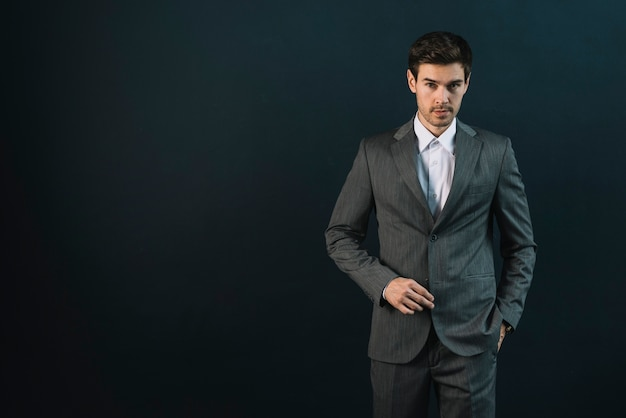 Homem jovem confiante com a mão no bolso contra o fundo preto Foto gratuita