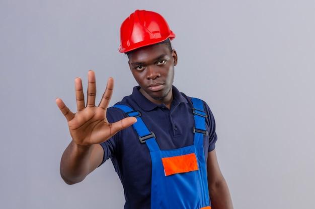 Homem jovem construtor afro-americano usando uniforme de construção e capacete de segurança em pé com a mão aberta fazendo sinal de pare com expressão séria e confiante gesto de defesa em pé Foto gratuita