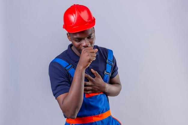 Homem jovem construtor afro-americano usando uniforme de construção e capacete de segurança, sentindo-se mal e tossindo em pé no branco isolado Foto gratuita