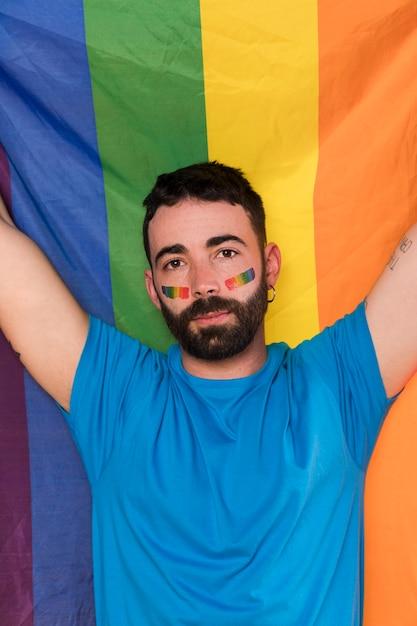 Homem jovem, contra, arco íris, bandeira Foto gratuita