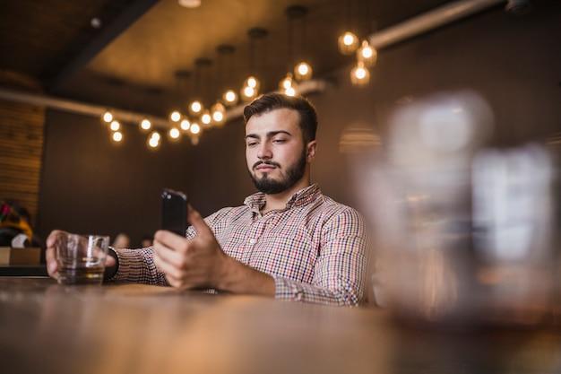 Homem jovem, copo segurando, de, bebida, usando, telefone móvel Foto gratuita