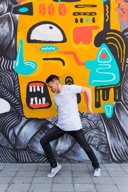 Homem jovem, dançar, contra, parede graffiti Foto gratuita