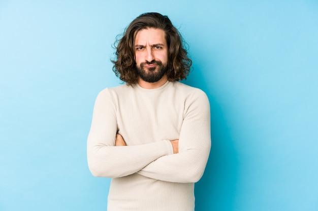 Homem jovem de cabelo comprido isolado em uma parede azul, rosto carrancudo em desgosto, mantém os braços cruzados. Foto Premium