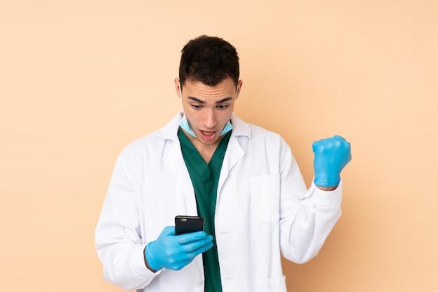 Homem jovem dentista segurando ferramentas na parede bege surpreso e enviando uma mensagem Foto Premium