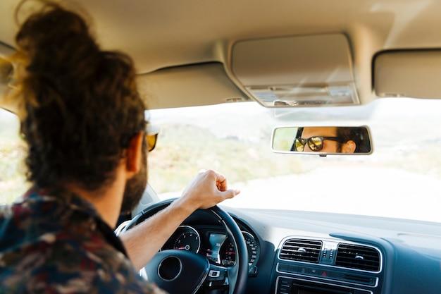 Homem jovem, dirigindo carro, ligado, dia ensolarado Foto gratuita