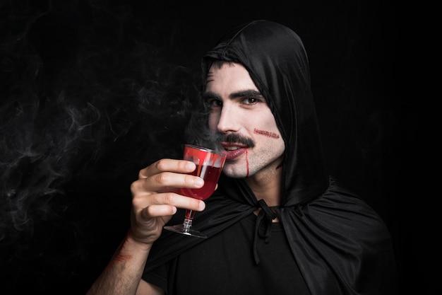 homem jovem em capa preta com cara branca bebendo fumegar