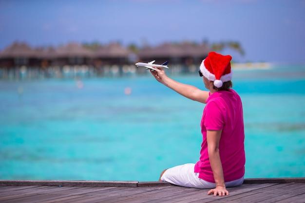 Homem jovem, em, chapéu santa, durante, praia, férias, ligado, madeira, jetty, com, miniatura, de, avião Foto Premium