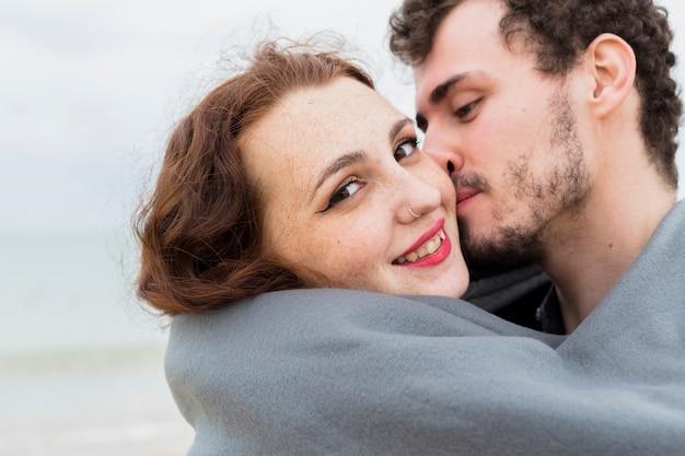 Homem jovem, em, cobertor, beijando, mulher, ligado, bochecha Foto gratuita