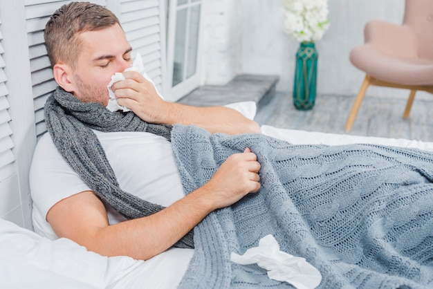 Homem jovem, encontrar-se cama, com, tecido, tendo, gripe, ou, alergia Foto Premium