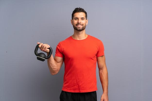 Homem jovem esporte fazendo kettlebell Foto Premium
