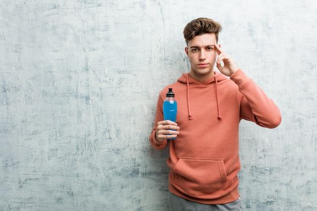 Homem jovem esporte segurando uma bebida energética, apontando seu templo com o dedo, pensando, focado em uma tarefa. Foto Premium