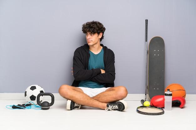 Homem jovem esporte sentado no chão em torno de muitos elementos de esporte pensando uma idéia Foto Premium