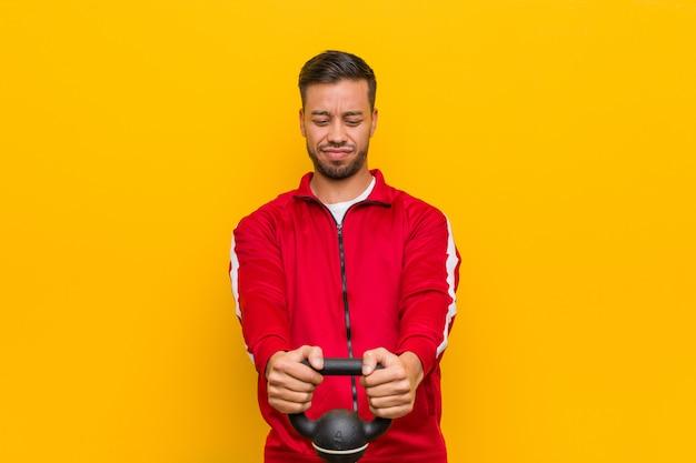 Homem jovem esporte sul-asiático segurando um haltere Foto Premium