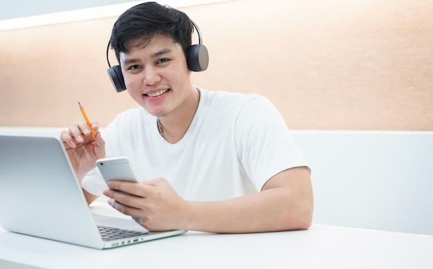 Homem jovem estudante asiática usando fone de ouvido, aprendendo o curso on-line Foto Premium