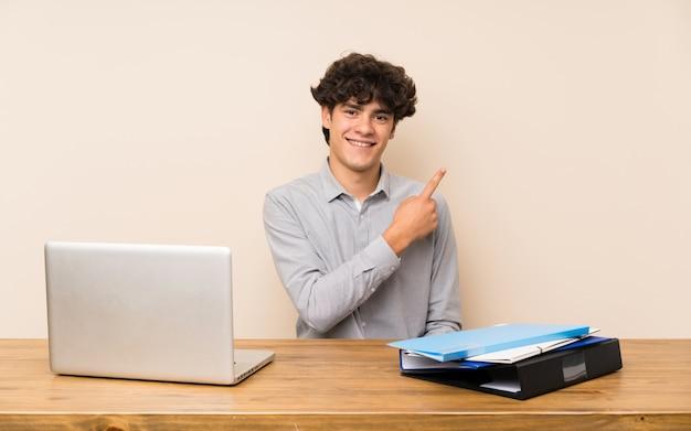 Homem jovem estudante com um laptop apontando para o lado para apresentar um produto Foto Premium