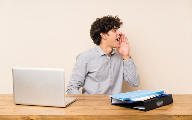 Homem jovem estudante com um laptop gritando com a boca aberta para a lateral Foto Premium