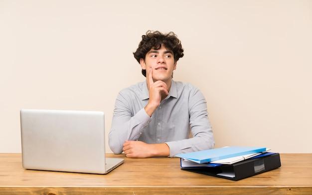 Homem jovem estudante com um laptop pensando uma idéia enquanto olhando para cima Foto Premium