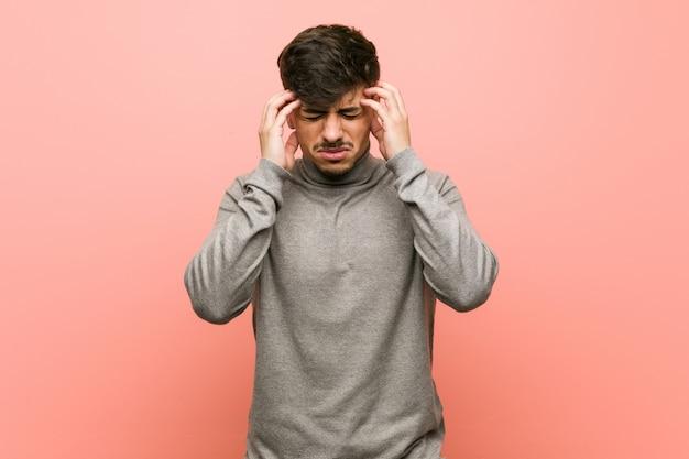 Homem jovem estudante inteligente tocando os templos e tendo dor de cabeça. Foto Premium