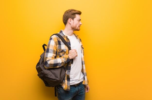 Homem jovem estudante ruiva do lado olhando para a frente Foto Premium