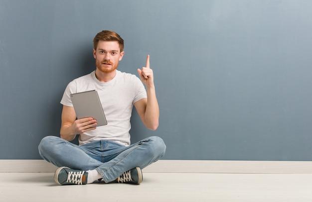 Homem jovem estudante ruiva sentada no chão, mostrando o número um. ele está segurando um tablet. Foto Premium
