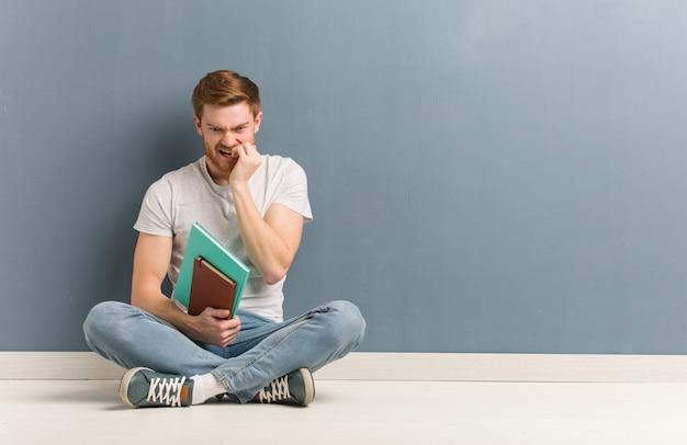 Homem jovem estudante ruiva sentada no chão roer unhas, nervoso e muito ansioso. ele está segurando livros. Foto Premium