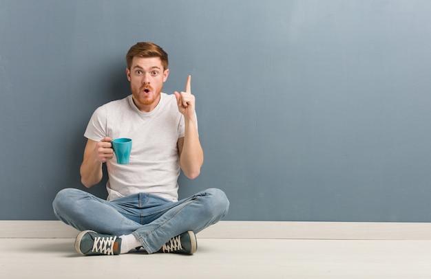 Homem jovem estudante ruiva sentada no chão, tendo uma ótima idéia, conceito de criatividade. ele está segurando uma caneca de café. Foto Premium