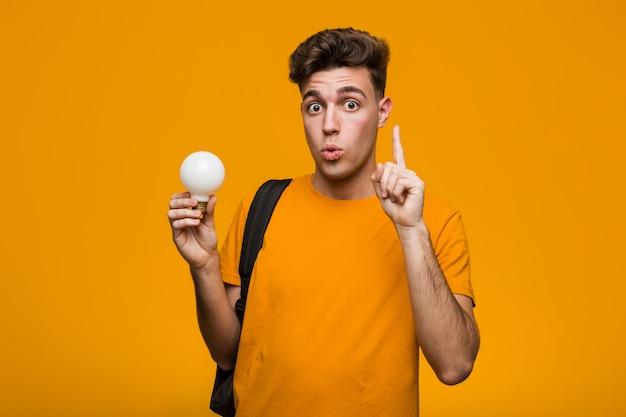 Homem jovem estudante segurando uma lâmpada relaxado pensando em algo olhando para um espaço de cópia. Foto Premium
