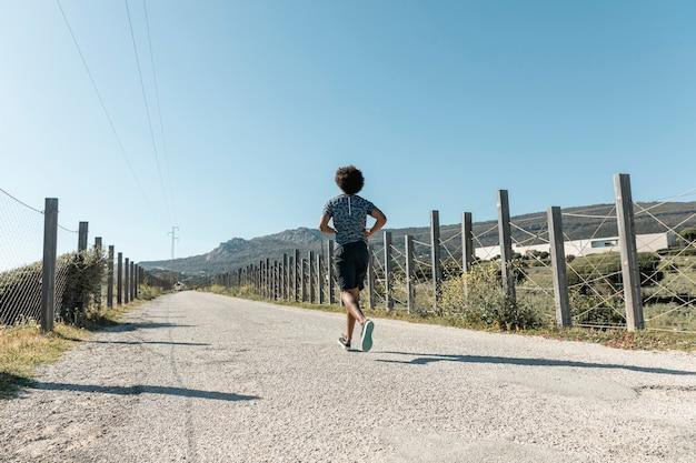 Homem jovem, executando, ligado, vazio, estrada rural Foto gratuita