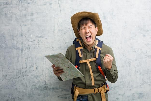 Homem jovem explorador chinês segurando um mapa surpreso e chocado Foto Premium