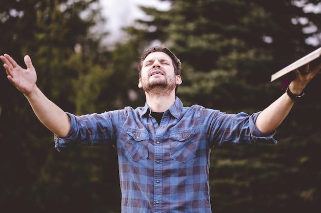 Homem jovem falando e segurando a bíblia nas mãos Foto gratuita