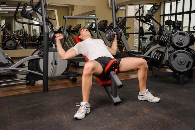 Homem jovem, fazendo, dumbbell incline, imprensa banco, malhação, em, ginásio Foto Premium