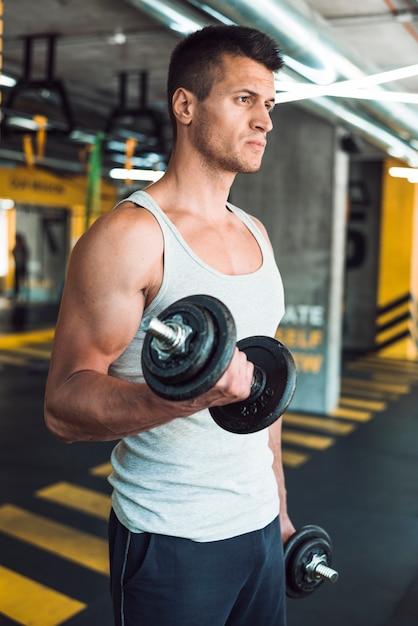 Homem jovem, fazendo, exercício, com, dumbbells Foto gratuita