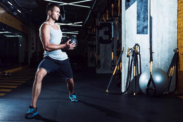 Homem jovem, fazendo, exercício, com, medicina, bola Foto gratuita