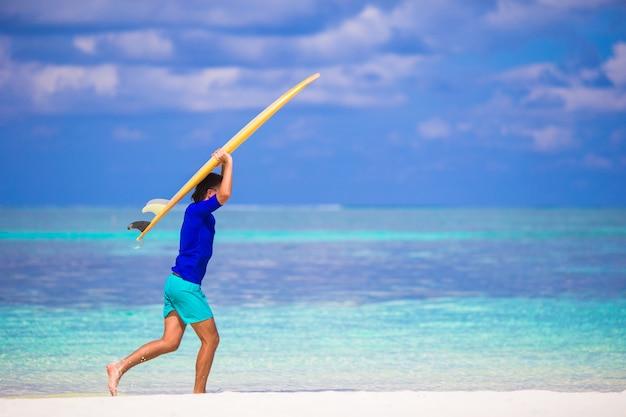 Homem jovem feliz surf na praia branca com prancha amarela Foto Premium