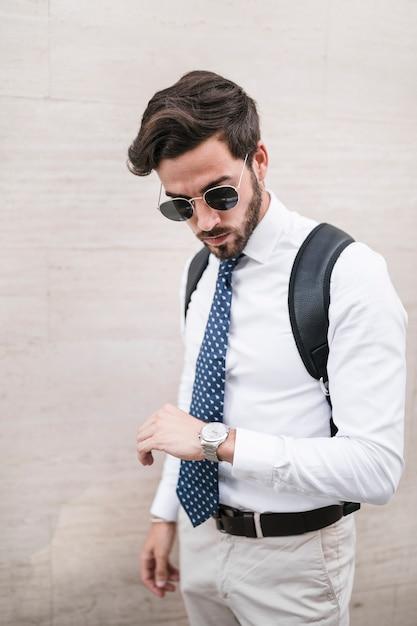Homem jovem, ficar, frente, parede, olhar, tempo, relógio Foto gratuita