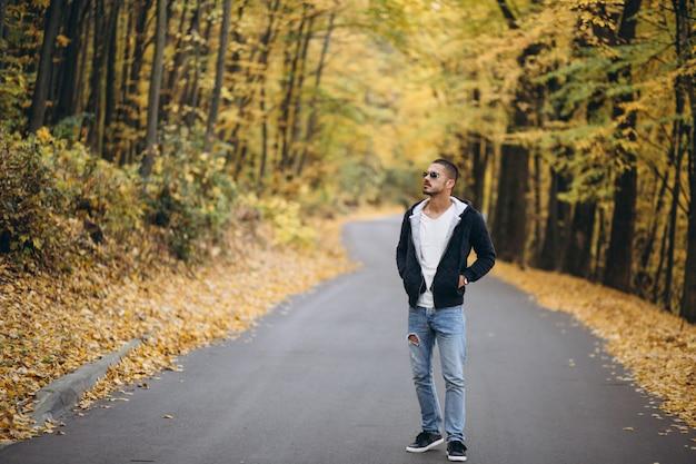 Homem jovem, ficar, ligado, um, estrada, em, um, outono, parque Foto gratuita