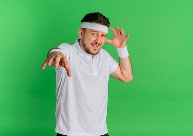 Homem jovem fitness com camisa branca e fita na cabeça, olhando para a frente, feliz e positivo, de mãos dadas em pé sobre a parede verde Foto gratuita
