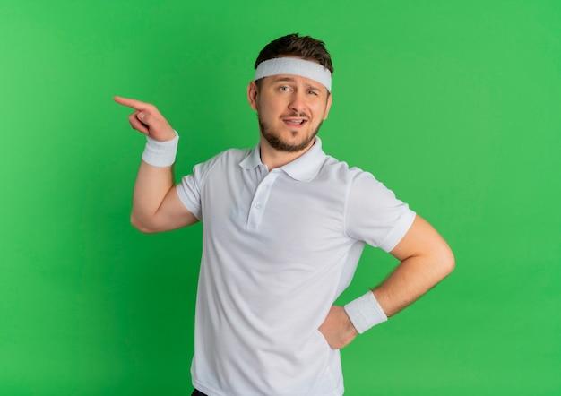 Homem jovem fitness com camisa branca e fita para a cabeça, olhando para a frente, apontando com o dedo para o lado em pé sobre a parede verde Foto gratuita