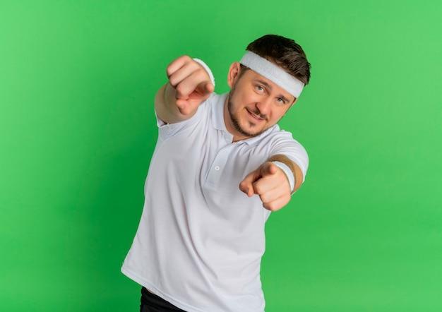 Homem jovem fitness em uma camisa branca com bandana olhando para a frente apontando com o dedo indicador para você com um sorriso no rosto em pé sobre a parede verde Foto gratuita