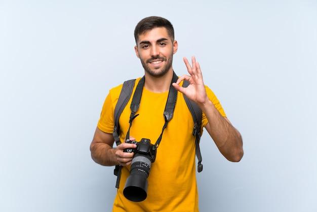 Homem jovem fotógrafo mostrando um sinal de ok com os dedos Foto Premium