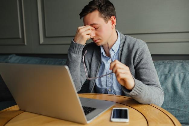 Homem jovem frustrado massageando o nariz e mantendo os olhos fechados durante o trabalho Foto gratuita