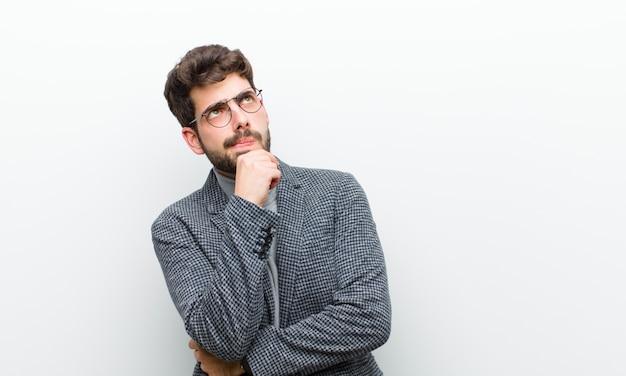 Homem jovem gerente pensando, sentindo-se duvidoso e confuso, com opções diferentes, imaginando qual decisão tomar parede branca Foto Premium