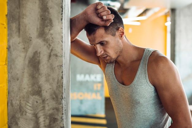 Homem jovem, inclinar-se, coluna, em, ginásio Foto gratuita