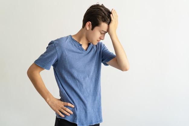 Homem jovem intrigado, segurando a testa enquanto se sente stress Foto gratuita