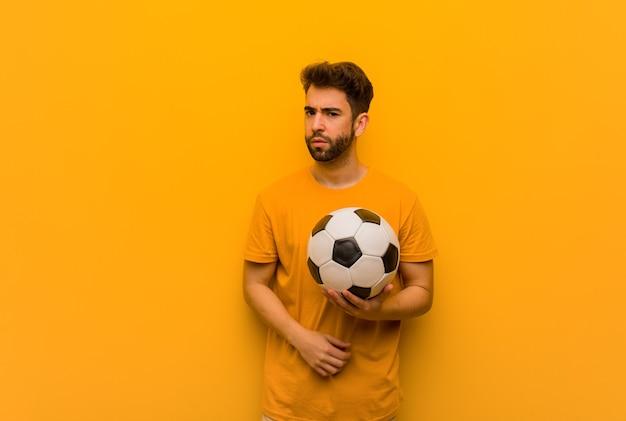 Homem jovem jogador de futebol olhando para frente Foto Premium