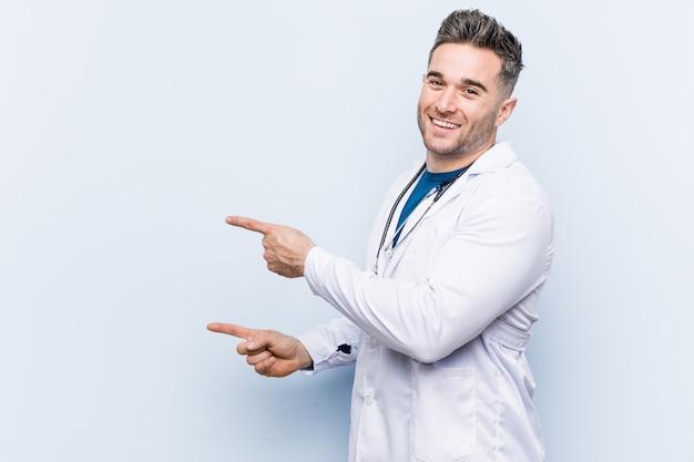 Homem jovem médico bonito animado apontando com o dedo indicador fora. Foto Premium