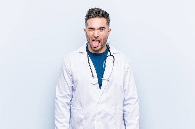 Homem jovem médico bonito engraçado e amigável saindo da língua. Foto Premium